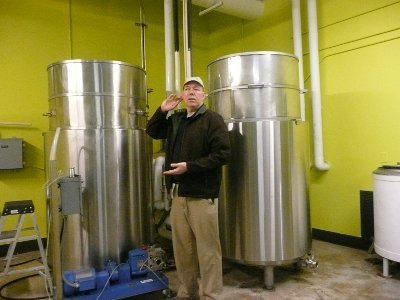 Greg Lorenz standing in front of two Moto tanks